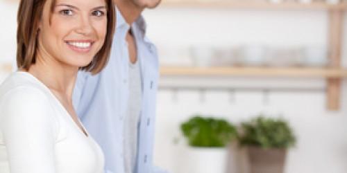 ein junges paar schneidet gemüse in der küche